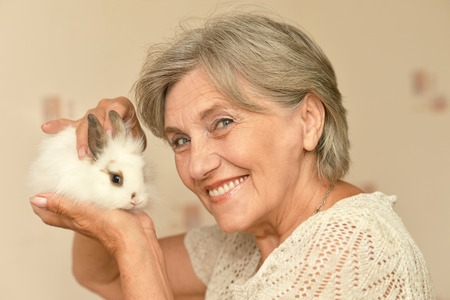 middle easter: Happy elderly woman with a little rabbit in her arm Stock Photo