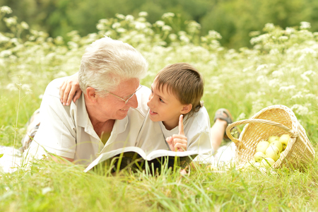grandson: Grandfather and his grandson reading book outdoor