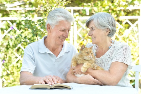 Happy senior couple on the veranda with cat