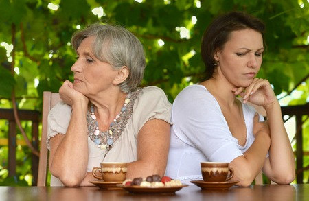 enmity: Senior mother and daughter sitting on the veranda and dont talk to each other