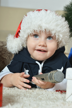 soloist: Little boy near new-year tree with microphone Stock Photo