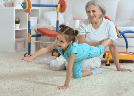 position d amour: femme �g�e et petite-fille faire de l'exercice � la maison