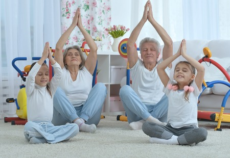 grandparents  and  little granddaughters doing exercise home Stock Photo