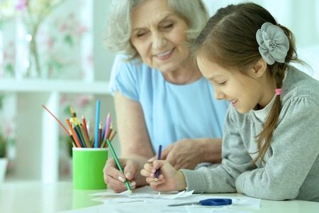 Portrait of a happy grandmother with granddaughter drawing together Foto de archivo