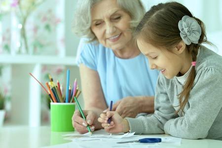 ni�os dibujando: Retrato de una abuela feliz con su nieta de dibujo juntos Foto de archivo