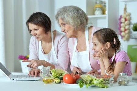 grey haired: happy women with little girl cooking in kitchen