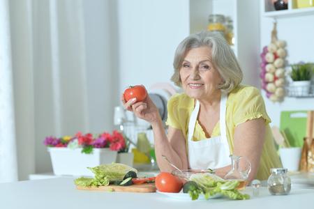 Senior vrouw met grijs haar koken in de keuken Stockfoto