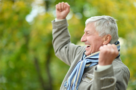 healthy seniors: Happy Senior man resting in the park in autumn