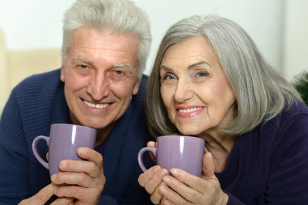 feeling happy: Portrait of an aged couple lying at floor with cups Stock Photo