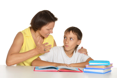 smiling child: Mother helping her teen son doing homework