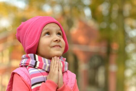 family with one child: Portrait of a little Girl prays autumn park Stock Photo