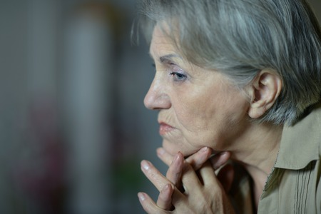 contagion: Portrait of sad aged woman at home close-up