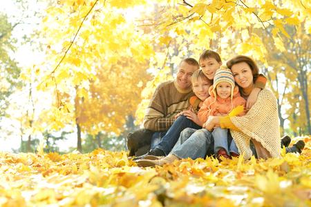 Happy family souriant de détente dans la forêt d'automne