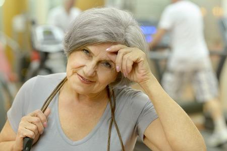 senior woman exercising: Cute smiling senior woman exercising in gym