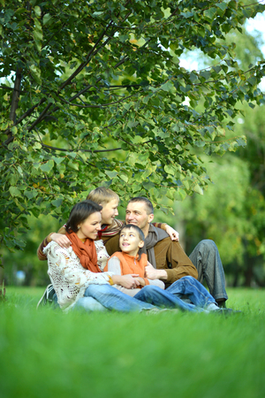 siting: Portrait of family resting in park,siting on grass