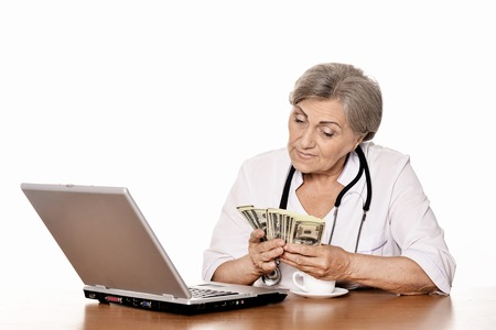 doctor money: Senior female doctor sitting at table with laptop and money