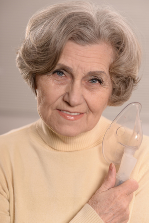 woman mature: Portrait of elderly woman with flu inhalation Stock Photo
