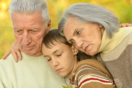 sad child: Sad grandparents with boy in the autumn park Stock Photo