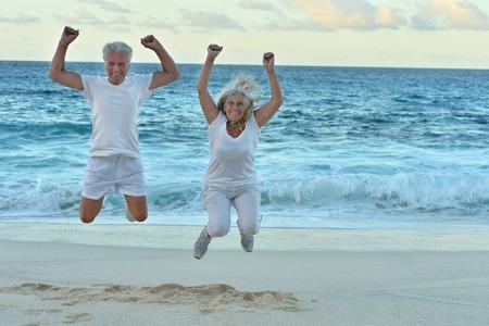 열 대 해변에서 점프하는 행복 한 노인 커플