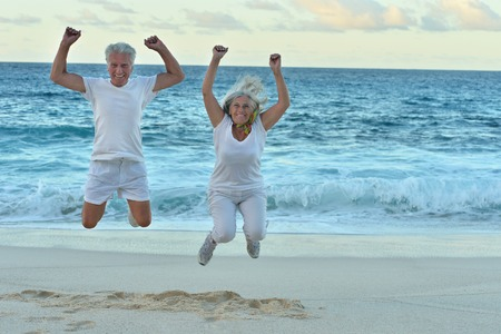 Happy elderly couple jumping  at tropical beach