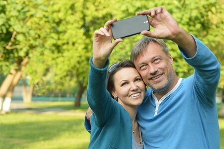 taking a wife: Portrait of a happy family taking selfie in park Stock Photo
