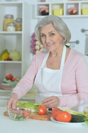 grey haired: Senior woman with grey hair cooking in kitchen
