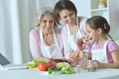 cooking food: happy women with little girl cooking in kitchen