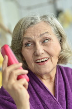 landline phone: Portrait of senior woman with mobile phone