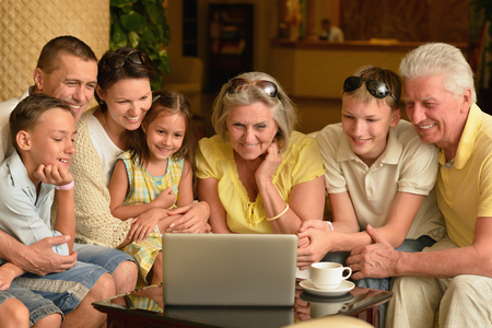 grandmother mother daughter: Portrait of a happy family sitting with laptop Stock Photo