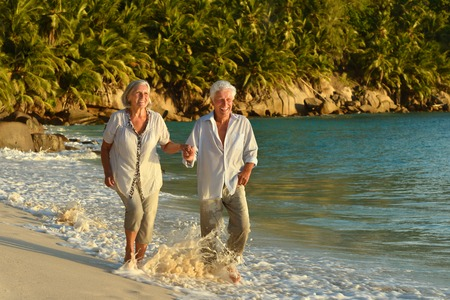 good grooming: Happy elderly couple rest at tropical beach at sunset