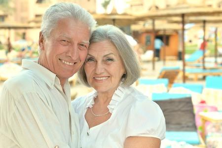 hotel resort: Senior couple relaxing near pool at hotel resort
