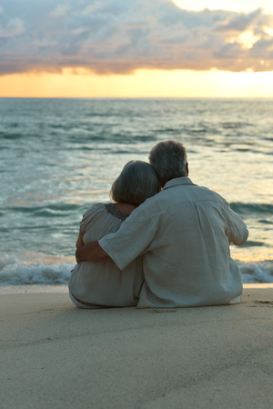 Happy elderly couple rest at tropical beach at sunset,back view