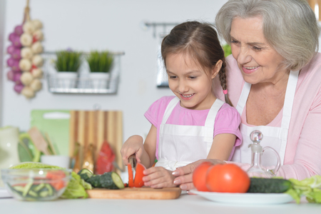 granddaughter: Senior woman with granddaughter cooking in kitchen Stock Photo