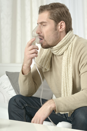 inhaler: Portrait Of Young Man Inhaling Through Inhaler Mask