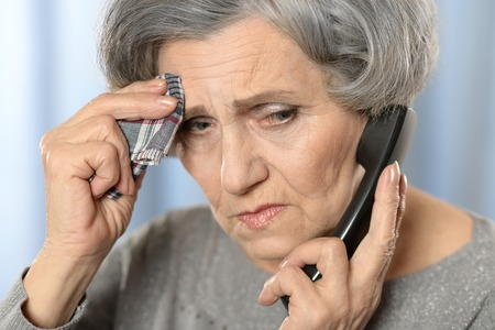 landline phone: Portrait of a sick mature woman calling doctor Stock Photo