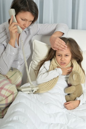 female child: Sick little girl with mother in bed at home