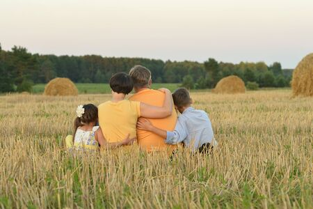 back view: happy family at summer  field back view