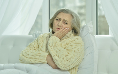 unwholesome: sick senior woman  in bed at home Stock Photo
