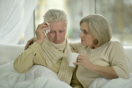 70s adult: Portrait of sick  elderly couple in bed Stock Photo