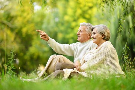 Hermosas ancianos feliz sentado en el parque de verano. El señalar