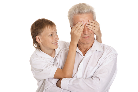 closes eyes: Grandfather and grandson, boy closes grandfather eyes on white background