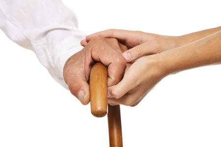 old age care: Young and old hands on cane together closeup against white background