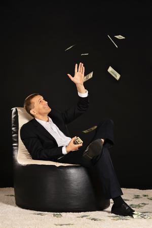 mucho dinero: Hombre de negocios sentado en un sill�n con un mont�n de dinero