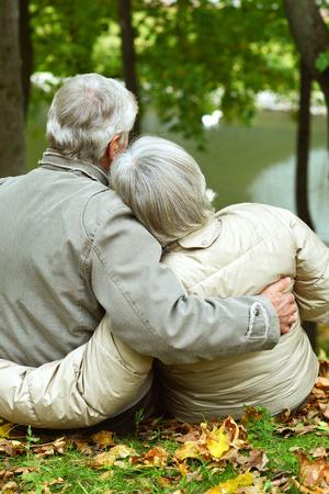 back view: Mature couple sitting near lake back view Stock Photo