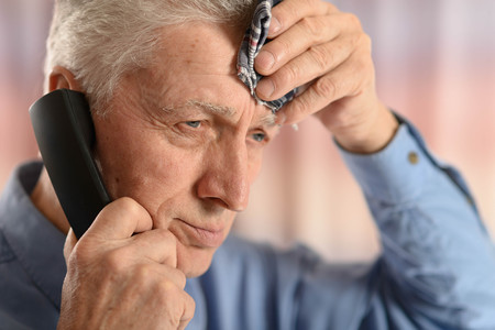 landline phone: portrait of a sick old man calling doctor Stock Photo