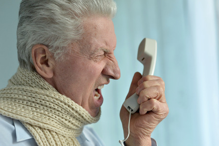 wroth: Portrait of an angry senior man with phone
