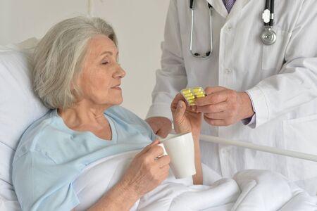 amiable: Senior woman portrait in hospital taking pills