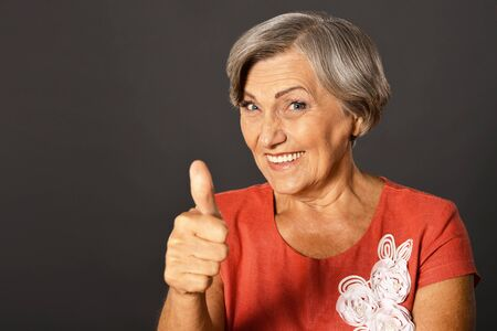 posing  agree: Portrait of elderly woman showing thumb up Stock Photo