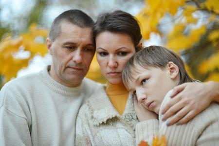 personas tristes: triste familia de tres en la naturaleza