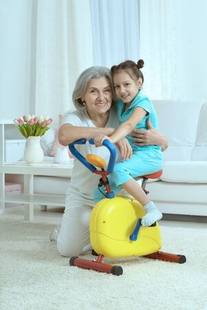 position d amour: senior woman and  little granddaughter doing exercise home